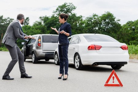 businesspeople quarreling and gesturing on road after car accident