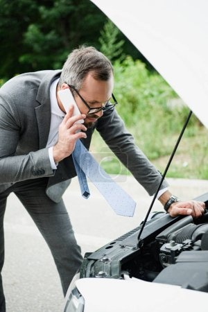 businessman talking by smartphone and looking in open car hood