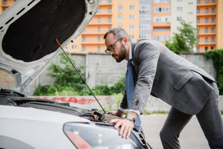 Photo for Side view of handsome businessman leaning on open car hood - Royalty Free Image