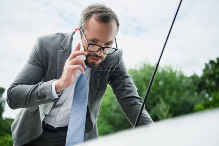 Photo for Handsome businessman talking by smartphone and looking in open car hood - Royalty Free Image