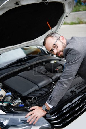 handsome businessman leaning on open car hood and looking at camera