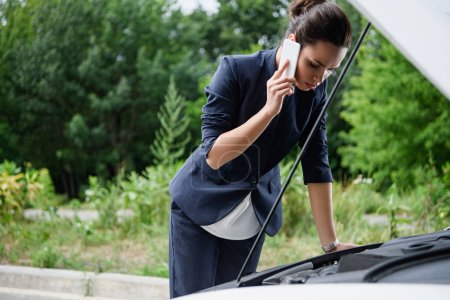 attractive businesswoman talking by smartphone and looking in open car hood