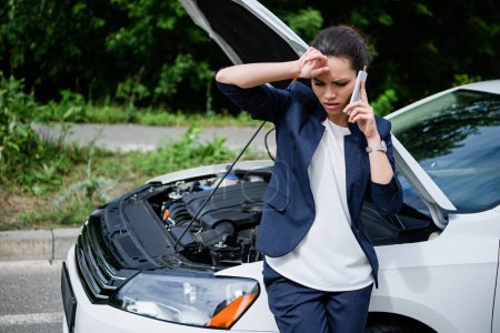 Photo for Tired businesswoman talking by smartphone near broken car with open hood - Royalty Free Image