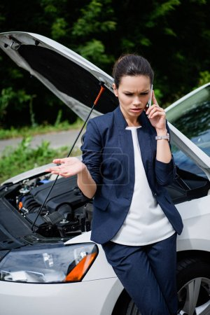Photo for Angry businesswoman talking by smartphone near broken car - Royalty Free Image