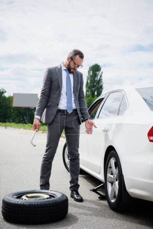 Photo for Handsome man looking at broken car and tires on road - Royalty Free Image