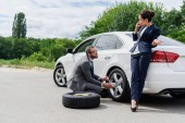 handsome businessman changing tires on car on road, businesswoman talking by smartphone