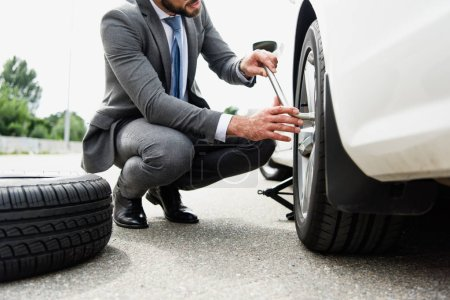 cropped image of businessman changing tires on car on road