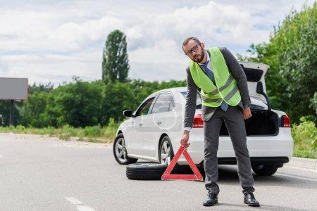 handsome businessman in light green vest putting stop sign on road near broken car