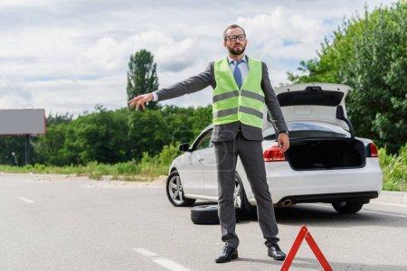 handsome businessman in light green vest stopping car on road