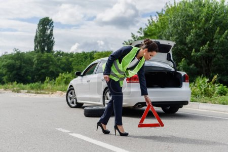 Photo for Attractive businesswoman in light green vest putting stop sign on road near broken car - Royalty Free Image