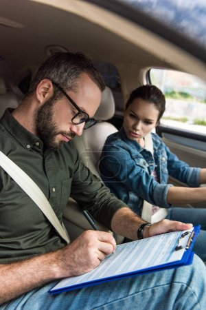 teacher writing something to clipboard during driving test