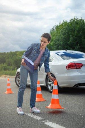 Foto de Mujer atractiva celebración de seguro de coche y poniendo conos de tráfico en carretera - Imagen libre de derechos