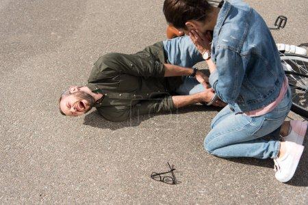 Photo pour Pilote regardant biker crier après l'accident de voiture sur route - image libre de droit