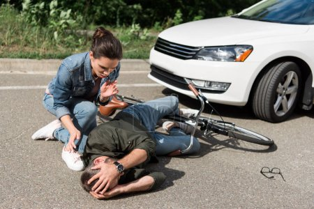 female driver helping male biker after car accident on road