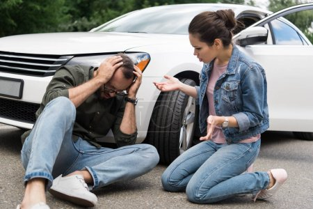 driver sitting near man on road after car accident