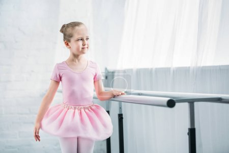 beautiful child in pink tutu practicing ballet and looking away in ballet school