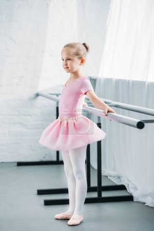 Photo for Side view of kid in pink tutu practicing ballet and looking away in ballet studio - Royalty Free Image