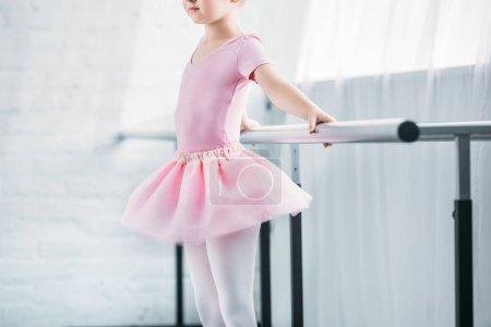 cropped shot of kid in pink tutu practicing ballet in studio