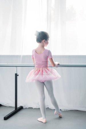 rear view of little kid in pink tutu practicing ballet in ballet school