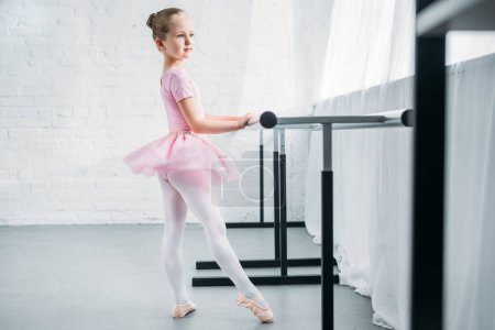 side view of adorable little ballerina in pink tutu practicing ballet and looking away