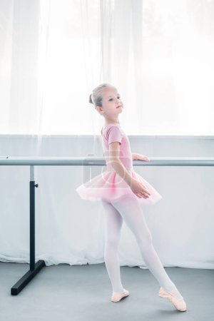 Photo for Adorable little ballerina in pink tutu practicing ballet and looking away - Royalty Free Image
