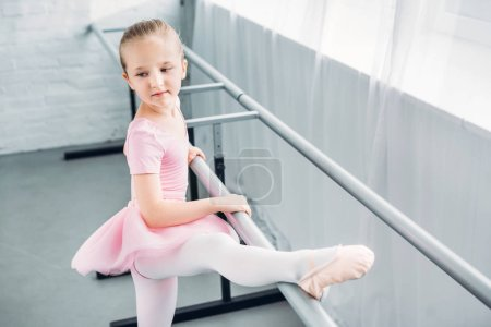 adorable kid in pink tutu stretching and practicing in ballet school