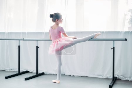 back view of little child in pink tutu exercising in ballet school