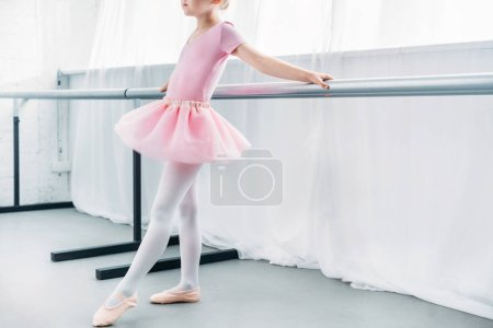 cropped shot of adorable little ballerina in pink tutu practicing in ballet studio