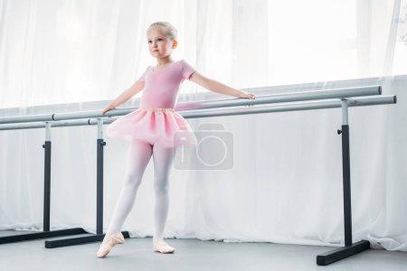 adorable little ballerina in pink tutu practicing in ballet studio