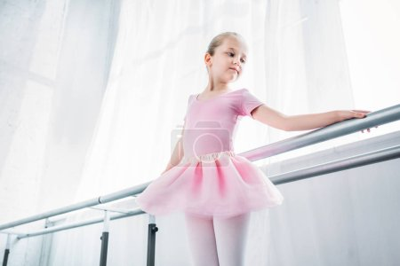 low angle view of adorable child in pink tutu practicing in ballet studio