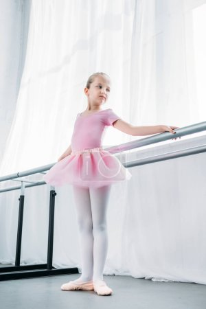low angle view of adorable little ballerina in pink tutu practicing in ballet studio