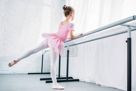 cute little ballerina in pink tutu practicing in ballet studio