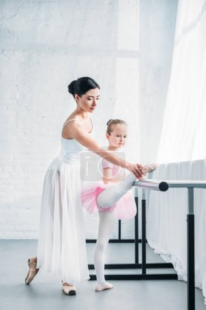 adorable child in pink tutu stretching while practicing ballet with teacher