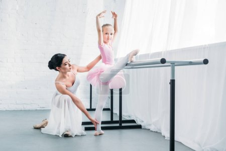 adorable child in pink tutu stretching and looking at camera while practicing ballet with teacher