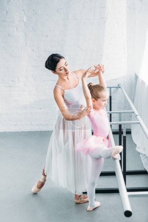 high angle view young ballet teacher exercising with adorable child in ballet studio