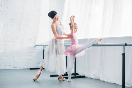 young ballet teacher exercising with cute little student in ballet studio