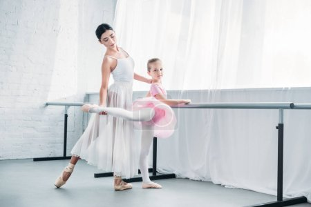 Photo pour Bel enfant en tutu rose pratiquer ballet avec jeune professeur au studio ballet - image libre de droit