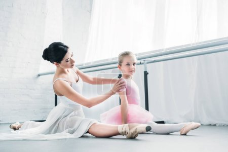 Photo for Adorable little ballerina in pink tutu sitting and stretching while training with ballet teacher in studio - Royalty Free Image