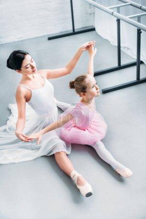 Photo pour Vue d'angle élevé de ballerine adulte exerçant avec mignon petit enfant en tutu rose à l'école de ballet - image libre de droit