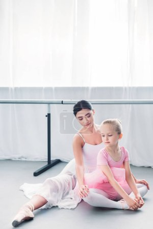 beautiful young ballerina looking at child in pink tutu exercising in ballet school