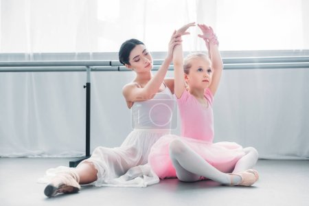 adult ballerina exercising with cute little child in pink tutu in ballet school