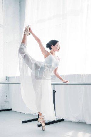 side view of graceful flexible young ballerina practicing ballet in studio