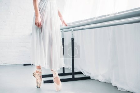 cropped shot of elegant young ballerina practicing ballet in studio