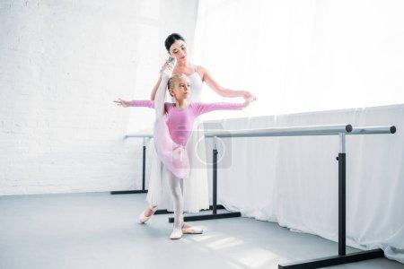 adorable little ballerina in pink tutu exercising with teacher in ballet school