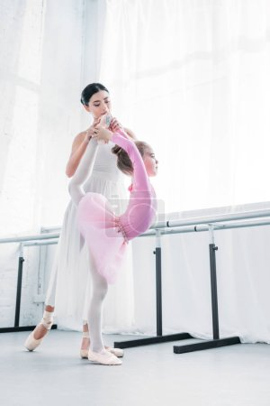 young ballerina training with child in pink tutu in ballet studio