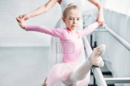 cropped shot of adult ballerina training with child in pink tutu in ballet studio