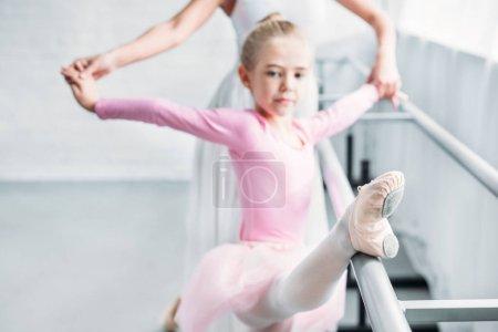 Photo pour Recadrée tir de ballerine adulte formation avec enfant en tutu rose en studio de ballet - image libre de droit