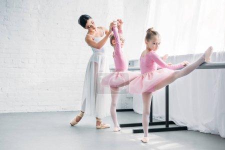 beautiful young ballet teacher exercising with kids in ballet school