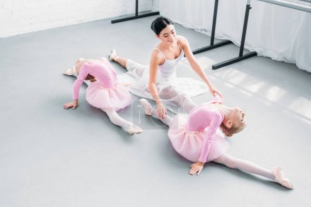 high angle view of smiling young teacher with cute little ballerinas exercising in ballet school