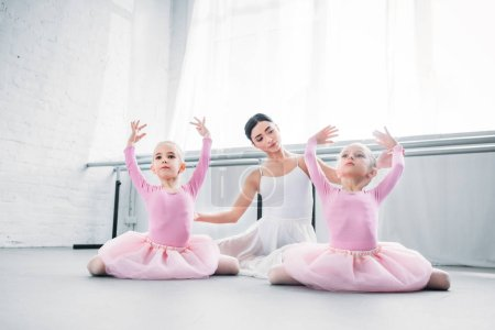 young ballet teacher looking at cute little kids in tutu skirts practicing ballet in school
